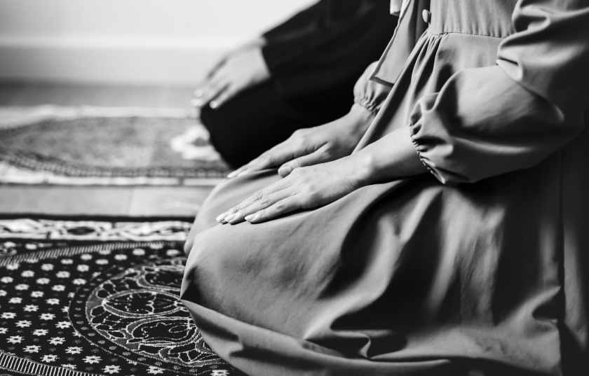 grayscale photography of woman kneeling on area rug